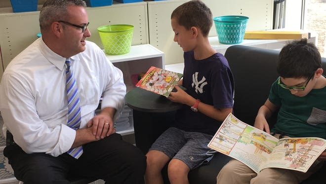 Principal Robert Buck talks books with fifth-graders at Wilson Elementary School in Anderson Township Sept. 5, 2017.