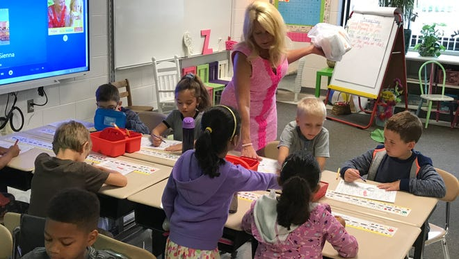 First-grade teacher Cheryl Zuzo encourages her students on the first day of school.