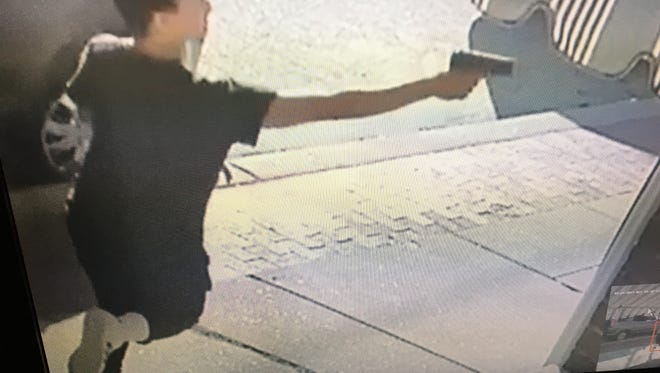 A photo of a paused video shows a person firing a gun toward a rowhome on Fifth Street in Wilmington's Little Italy neighborhood on Monday.