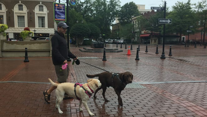 Steve, Lauer, of Naples, Florida, walks his dogs through downtown Greenville on Sept. 11, 2017.