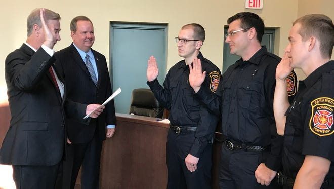 Plymouth Township Clerk Jerry Vorva (left) swears in new firefighters Adam Gwynn, Anthony Schoenherr and Tyler Caswell.