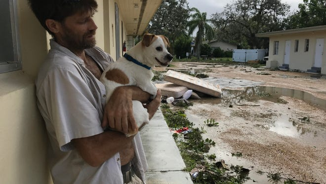 Thomas Garrigus, 45, holds his dog, Peanut, outside of their apartment in downtown Bonita Springs on Monday. Hurricane Irma caused the apartment's ceiling to collapse, which caused damage to Garrigus' belongings.