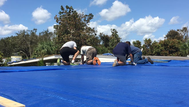 A crew of volunteers from the Church of Jesus Christ of Latter-day Saints, Rockledge ward, installs a tarp on the roof of a Cocoa home and garage.