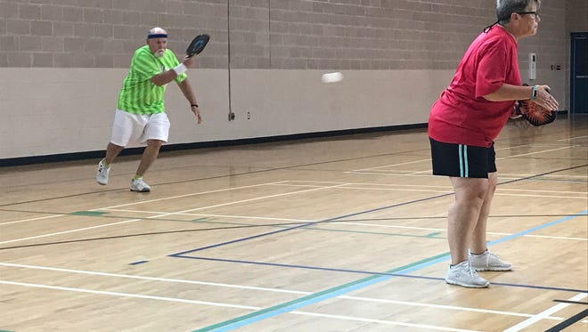 """Mike Hogg, left, returns a pickle ball shot as his wife and playing partner Sue Hogg watches the net on Friday, Sept. 15, 2017, at the William J. """"Red"""" Vickrey Resource Center in Pensacola. The couple participated in pickle ball, one of 21 events at the Pensacola Senior Games."""