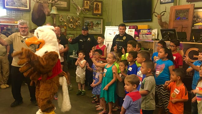 Kids and local law enforcement dance with Eddie Eagle while learning about gun safety.