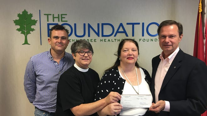 From left:Johnathan Kendrick, the Rev. Gayle McCarty, Dr. Susan Francisco andFrank McMeen Sept 18, as St. Luke's presents check for Dispensary of Hope.