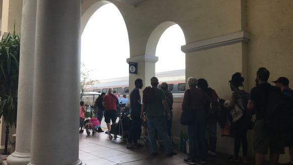 Passengers line up for an arriving Amtrak train at