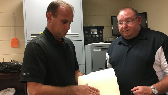 Investigator Jason Clark, left, shows logs that track evidence kept at the Sheriff's Office as Houston County Sheriff Kevin Sugg looks on.