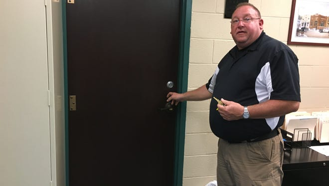 Houston County Sheriff Kevin Sugg shows the door to his department's evidence room, which requires two keys to open. He is his holding a key to the office in which its located and explains that only Investigator Jason Clark currently has keys to unlock the door.