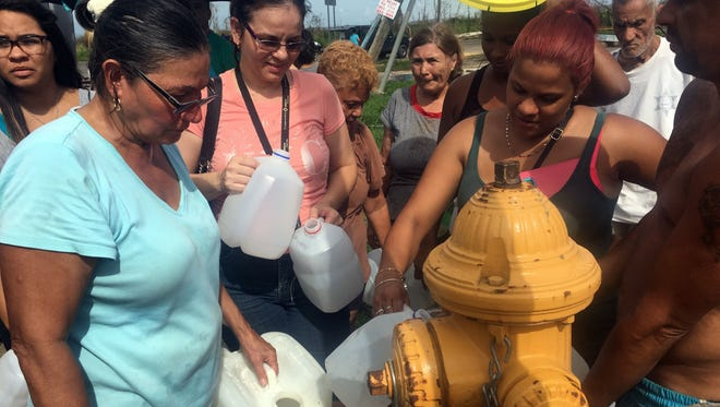 Residents of Arecibo, Puerto Rico, line up to siphon drinking water from a fire hose attached to a hydrant on Sept. 23.