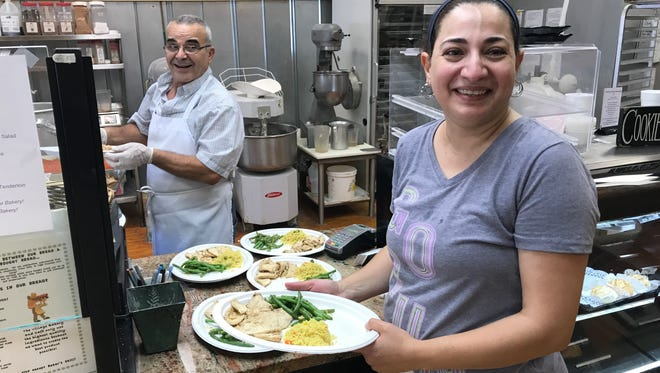 Abdoul and Amani Karkour serve up Syrian-style food at a hurricane relief fundraiser at their restaurant, the Village Bakery and Cafe in Pendleton.