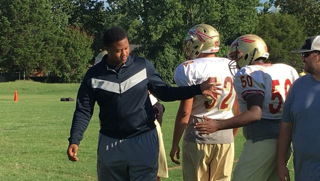 Riverdale senior D'Andre Litaker (left) shows support to players during Wednesday's practice. The University of Tennessee commitment tore his right ACL and is out for the season.