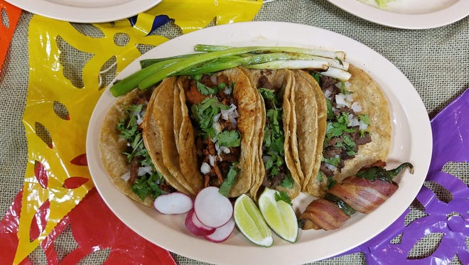 Tacos Juarez (Pork al pastor and steak) are served with grilled green onions, radish slices, lime wedges and a bacon-wrapped jalapeno pepper. Find them at Fiesta Evansville this weekend.