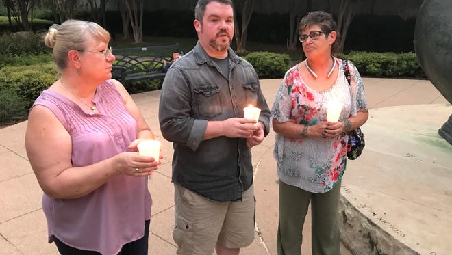 Stephen Garvin, center, speaks up during a candlelight vigil for Las Vegas shooting victims and heroes while Karin Alger, left, and Pastor Leslie Dunlap, right, all of Grace Lutheran Church on Pioneer Drive, listen to his message of ending the violence. They attended the Indivisible Abilene vigil at Everman Park on Wednesday, Oct. 4, 2017.