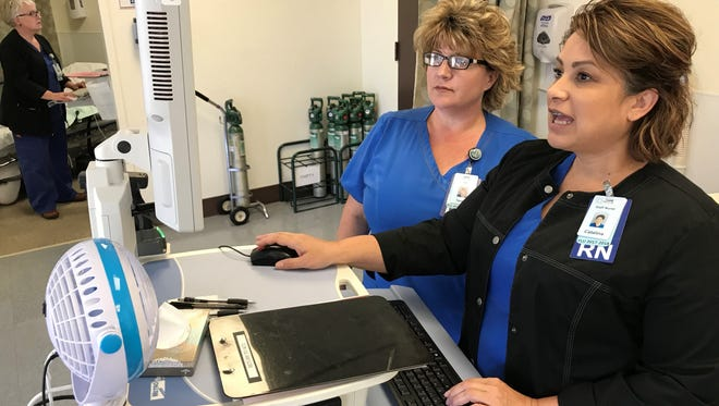 Registered nurses, Teresa Berbereia, left, and Catalina Ramirez input patient information in a wing of the hospital.