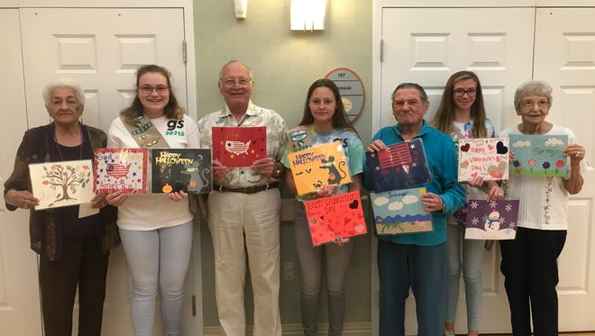 Pillar Castillo, Megan Granum, Gerald Susdorf, Kara Bradley, Neil London, Katie Earle and Ann Barnes display some of the snack mats the Girls Scouts shared with the Council on Aging's adult day care program.