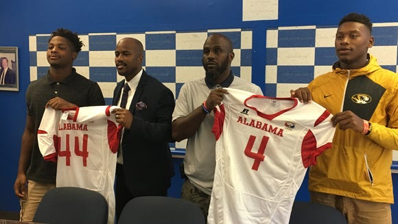 Sidney Lanier linebacker La'Dedric Jackson, far left, and quarterback James Foster, far right, pictured with their jerseys for December's Alabama-Mississippi all-star football game.
