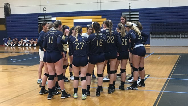 The Roxbury volleyball team talks things over during a timeout.