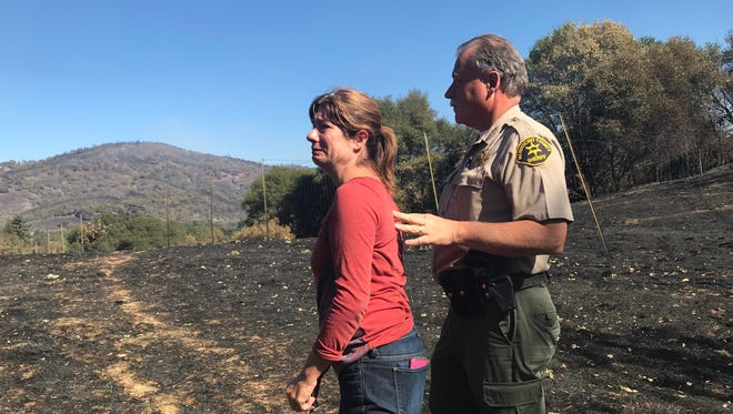 Cassie Taaning-Trotter looks at the damage behind her property as Sheriff Tom Allman with the Mendocino County Sheriff's Office consoles her.