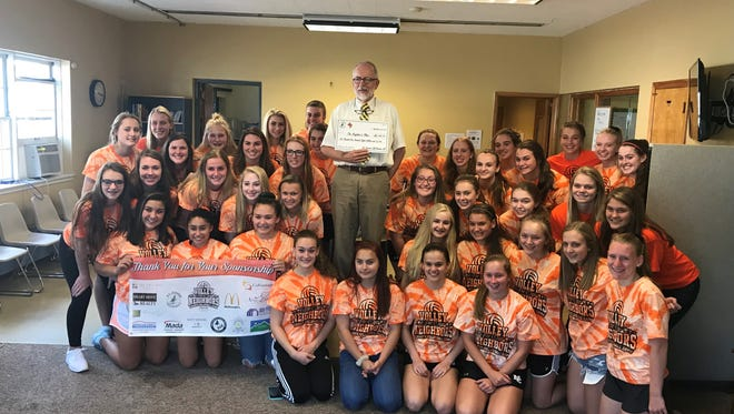 D.C. Everest and Newman Catholic volleyball players present a check for $6,108.75 toTom Rau of The Neighbors' Place.