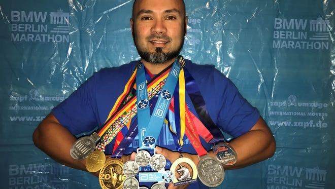 Woodlawn, NSU Nursing School graduate Shane Bison displays his Six Star medal earned for completing a string of marathons.