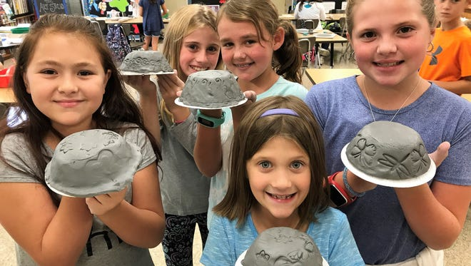 """Cienna Lupoldi, Layla Stickel, Michaela McLaughlin, Rosie Weichmann, Lacey Kressley, members of Main Road School's third and fourth grade Art Club, show off their creations for Delsea Regional School District's community project, """"Empty Bowls."""" Ryan Looby is in the background."""
