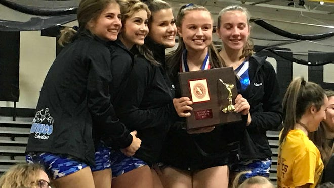 Members of the Wayne Valley gymnastics team smile with the county championship trophy.