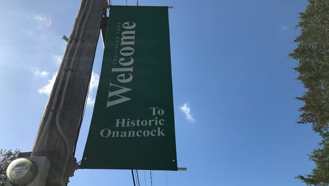 "Green ""welcome"" signs are interspersed with Onancock's new historic banners on Market Street. The project by the town's decorating committee features six historic sites around town in pen and ink drawings."