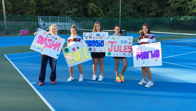 The five girls tennis seniors for Verona pose with posters made by teammates following a victory over Cedar Grove.