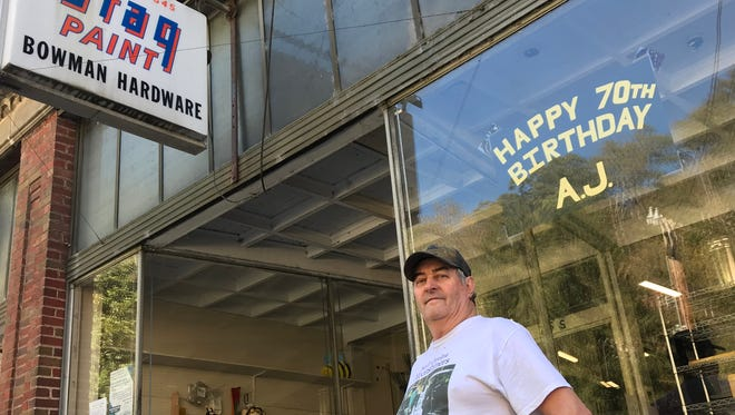 """Longtime Bowman Hardware employee A.J. Bridges stands below a sign put up by owner Cathy McCormick outside the South Main Street store. """"I feel 70,"""" he said days after celebrating his 70th birthday Oct. 21."""