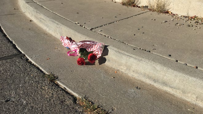 A bouquet is seen Friday morning at the intersection of East 20th Street and Cochiti Avenue, where a collision between a motorcycle and an SUV killed Donald Brandenburg, 53, of Farmington on Thursday evening.
