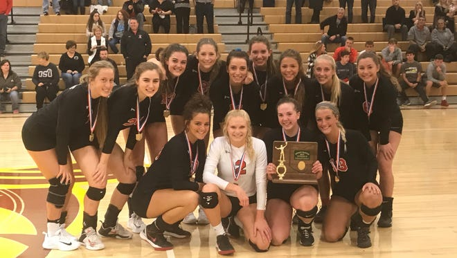 The Pleasant volleyball team poses with the Division III district championship trophy it earned Saturday afternoon at Buckeye Valley after beating Northmor 3-1.