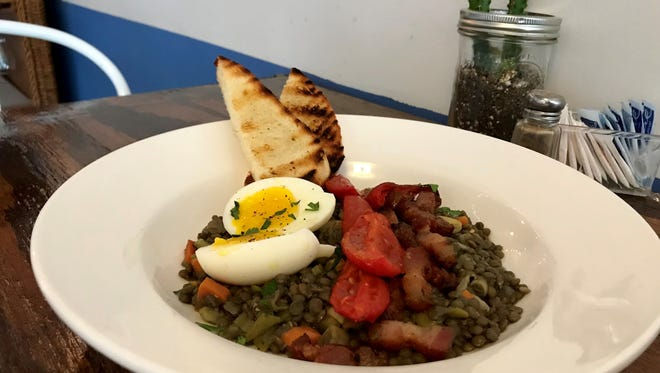 The French lentils from Desert Moon Cafe, 310 S. Florence St., are made with smoked bacon, green chile, tomatoes and topped with a soft boiled egg. The dish is served with a side of toasted French bread.