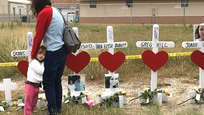 A woman hugs her daughter as they walk along a line of crosses memorializing the victims of the shooting at First Baptist Church in Sutherland Springs.