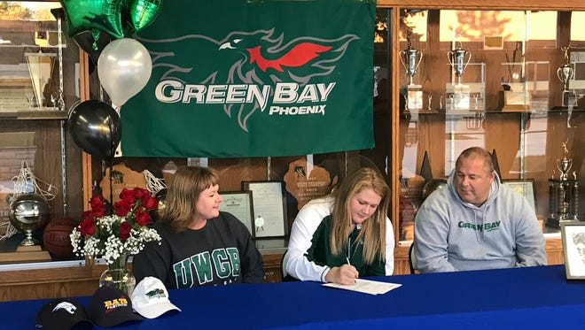 Oshkosh West senior Alyssa Brewer signs a letter of intent to continue her softball career at UW-Green Bay on Thursday. Brewer is joined by parents Steve and Jody.