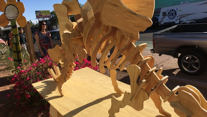 Wood dinosaur models are usually smaller than this one, seen at the Grand Avenue Festival on Nov. 11, 2017.