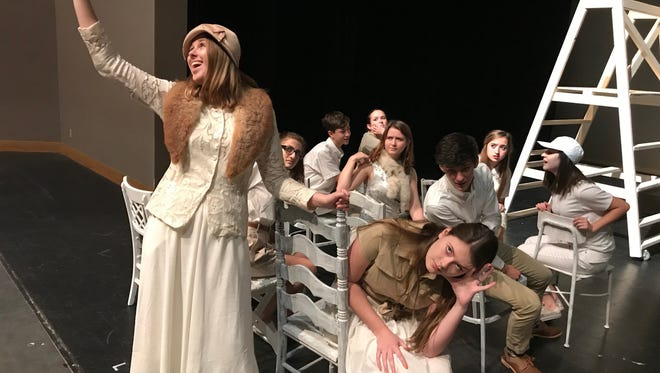 """Junior Ava Unti (with her arm raised) and senior Chloe McCarthy in a scene from """"Our Town."""""""