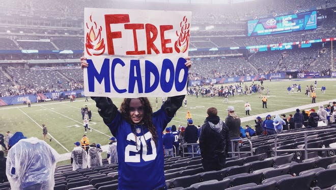 """Giants season ticket holder and West Milford resident Samantha Hollfelder, 18, holds a """"Fire McAdoo"""" sign in Section 117 of MetLife Stadium during the team's 51-17 loss to the Los Angeles Rams in East Rutherford on Sunday, Nov. 5, 2017."""