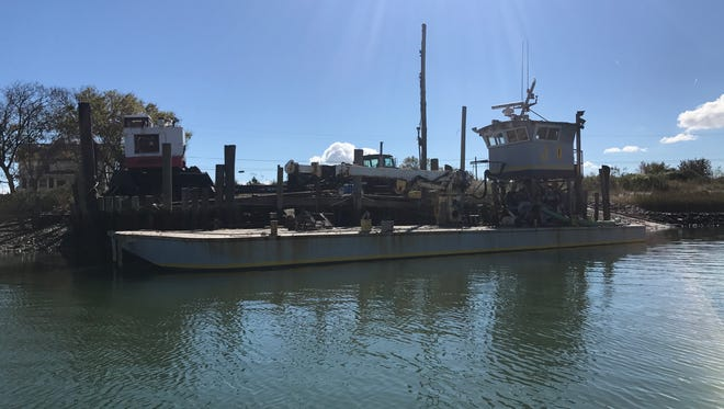 Northampton company SeaDuce uses a barge to transport dredged shell from deeper waters to the mudflats offshore from the village of Oyster. The privately funded project by The Nature Conservancy and the Virginia Marine Resources Commission is building 3 acres of new oyster reef, including 1 acre that will eventually open for public harvest.