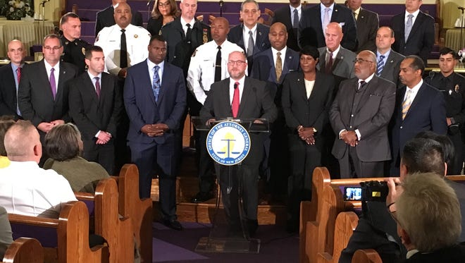 Attorney General Christopher Porrino, surrounded by law enforcement, community members and, left, former New York Giant Jessie Armstead to announce a new traffic safety initiative on Nov. 15, 2017.