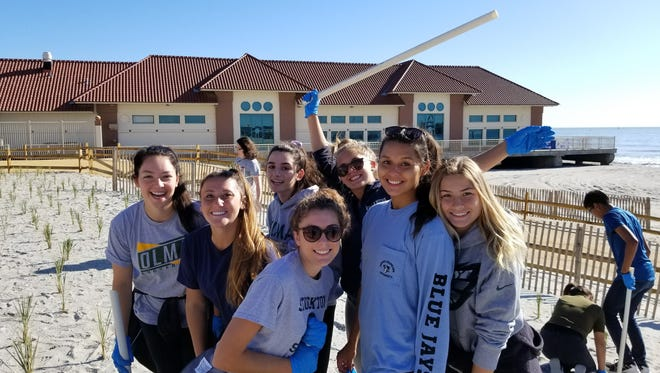 Our Lady of Mercy Academy seniors (from left) Allyson McCormick, Gianna Capriotti, Amanda Willis, Bianca Fiocchi, Victoria Smith, Gabriella Poe and Abigail Ward participated in Project Green, an annual Interact Club service project which involves planting dune grass on the beach in Atlantic City.
