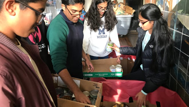 Student council members distribute the 10,000 canned goods they helped collect.