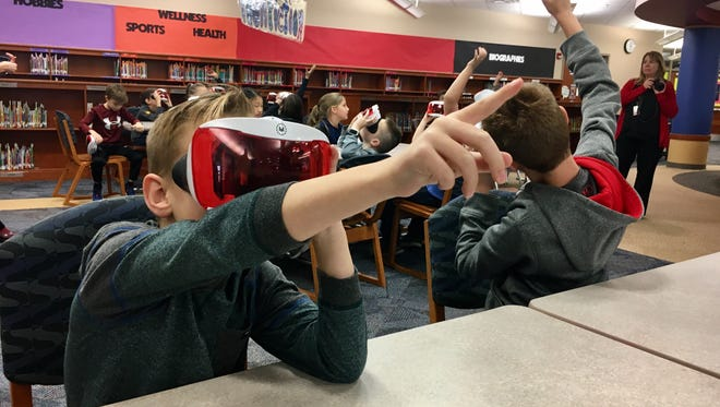 Third grader Jase Sickler can't help but point while trying on virtual reality goggles in Noble Crossing Elementary on Dec. 5. The class visited monuments in Washington D.C. as part of a government lesson.
