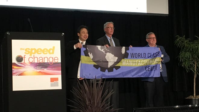 From left, Foxconn Director of U.S. Special Initiatives Alan Yeung, New North Executive Director Jerry Murphy and Lindquist Machine CEO Mark Kaiser hold up a NEW Manufacturing Alliance flag during the New North Summit at the KI Convention Center.