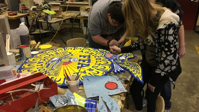 FFA members Travis Vaske, Kendall Howard and Alexis Bolton work on painting the FFA seal for their float in the Gallatin Christmas Parade.