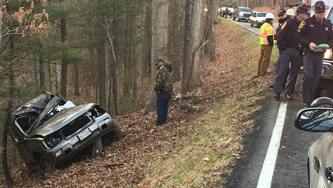 A tow-truck driver surveys the wreckage in a crash that killed two people Tuesday afternoon near Churchville.