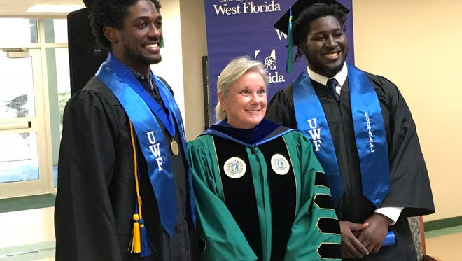 UWF football players Reggie Barnes (left) and Ronald Bell with school president Martha Saunders after she arranged for a special graduation ceremony Wednesday at the UWF president's office for the two seniors.