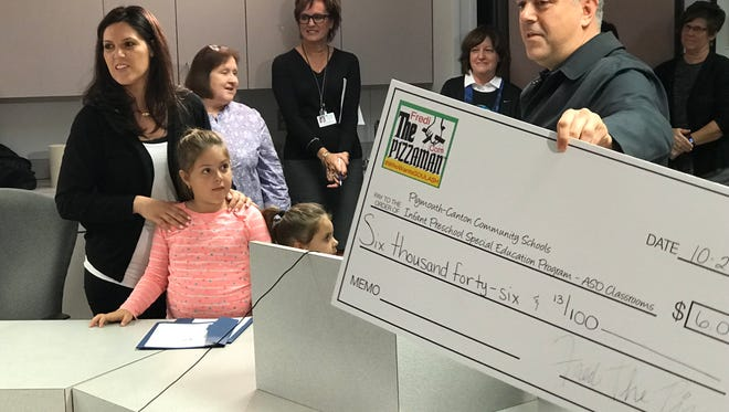 Fredi Bellow presents a check for more than $6,000 raised at a golf outing for Plymouth-Canton's Infant Preschool Special Education Program.