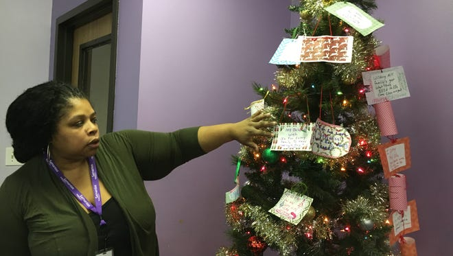 Samaritas Family Center program manager Tamieka Andrews looks at wishes placed on the center tree.