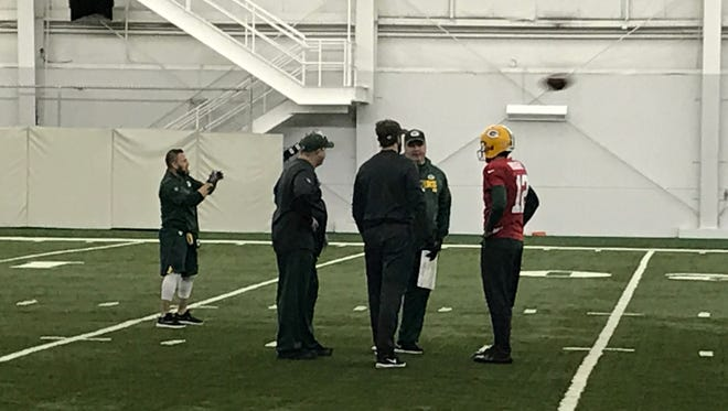 Aaron Rodgers consults with some Packers coaches during practice Thursday.